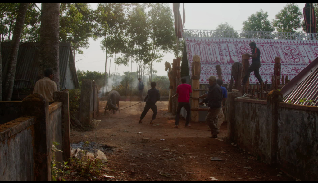 Film still from How To Improve The World. Wideshot of a wide dirt path with houses and wooden fences on either side, and trees in the background. There's Vietnamese people on the path and the fences.