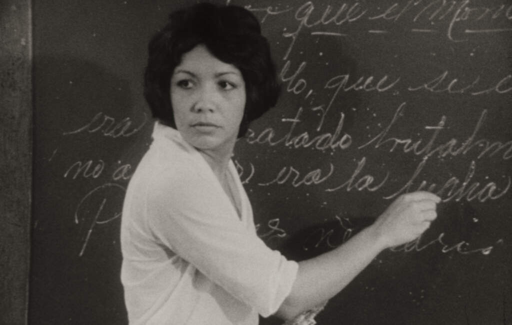 Black and white still from One Way Or Another. A woman in a white top and with black hair in a bob hairstyle. She's writing with chalk on a blackboard, and has her head turned over her shoulder as she's writing.