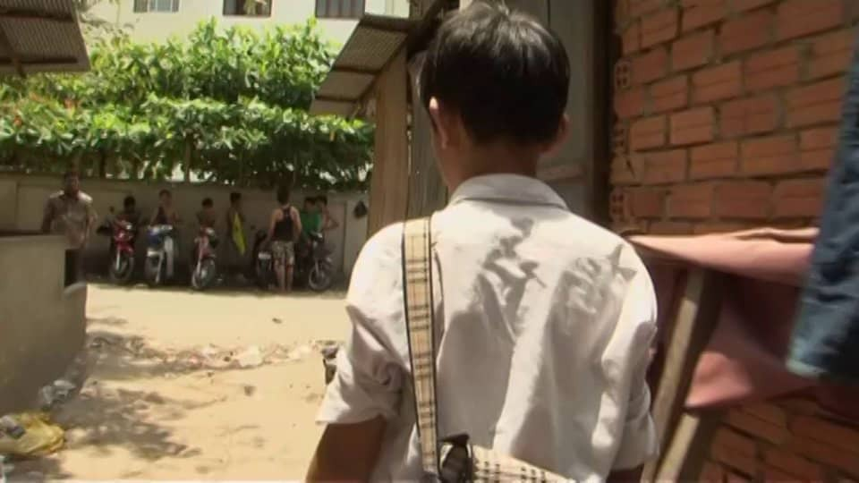 Film still from A Scale Boy. A wideshot of a young Cambodian boy with short black hair, wearing a white shirt and a schoolbag satchel over his shoulder. His back is facing the camera, and he's walking along a path next to a red brick building.