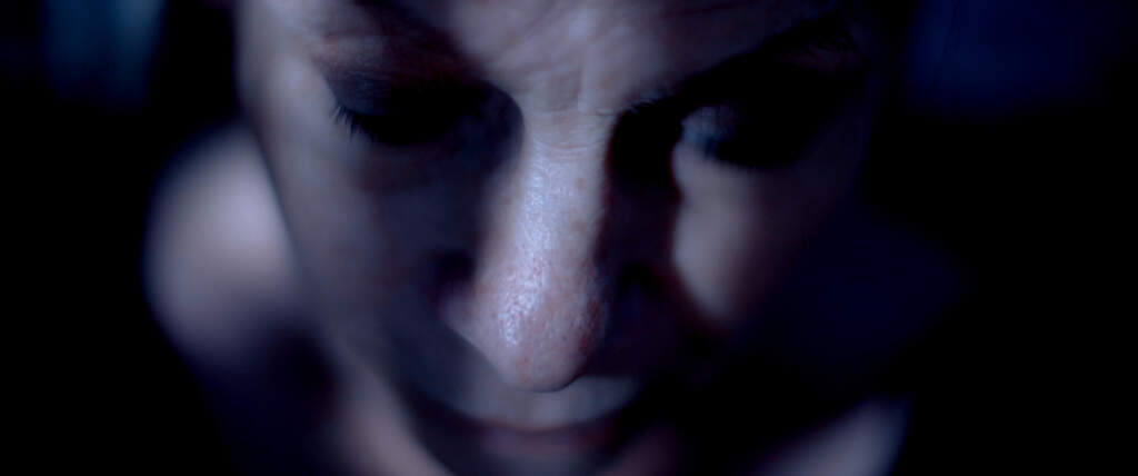 Still from Everyday Star. A black and white close up shot looking downwards onto someone's face, with shadows on their cheeks and the sides of their face. The middle of their face is illuminated by light.. On the left, the top of their shoulder is visible, but the rest of the still is submerged in darkness.