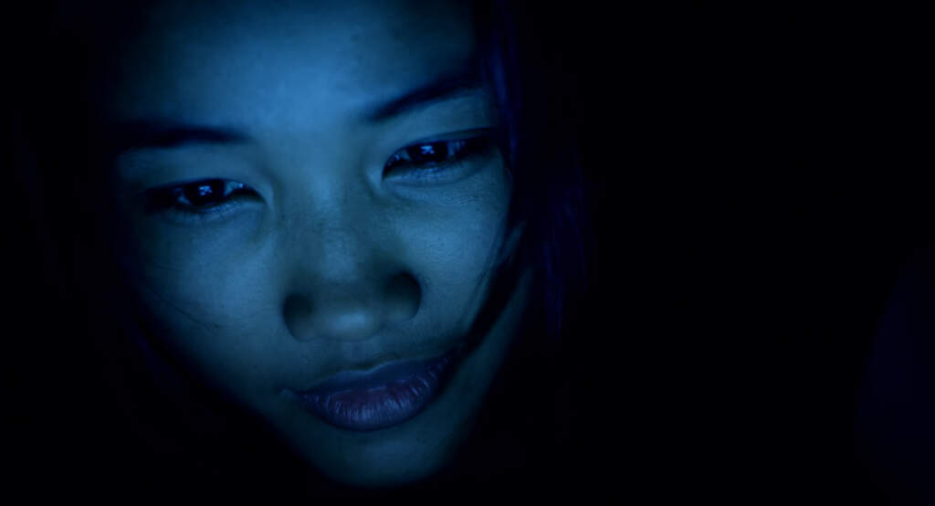 Film still from Cambodia 2099. On the left hand side, a close up shot of someone's face illuminated by a blueish light. The rest of the shot is submerged in darkness.
