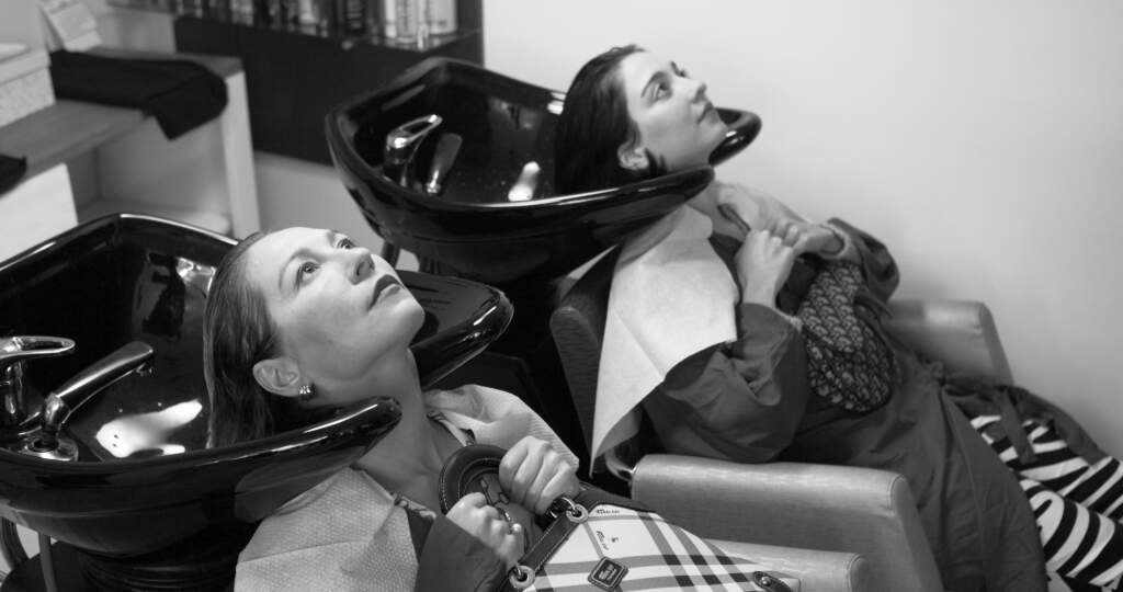 Film still from El Planeta. Black and white wideshot of two white women side by side at the hair salon, having their hair washed in separate basins. They both have wet hair, and are laying back with their heads in the basins, looking up to the ceiling.