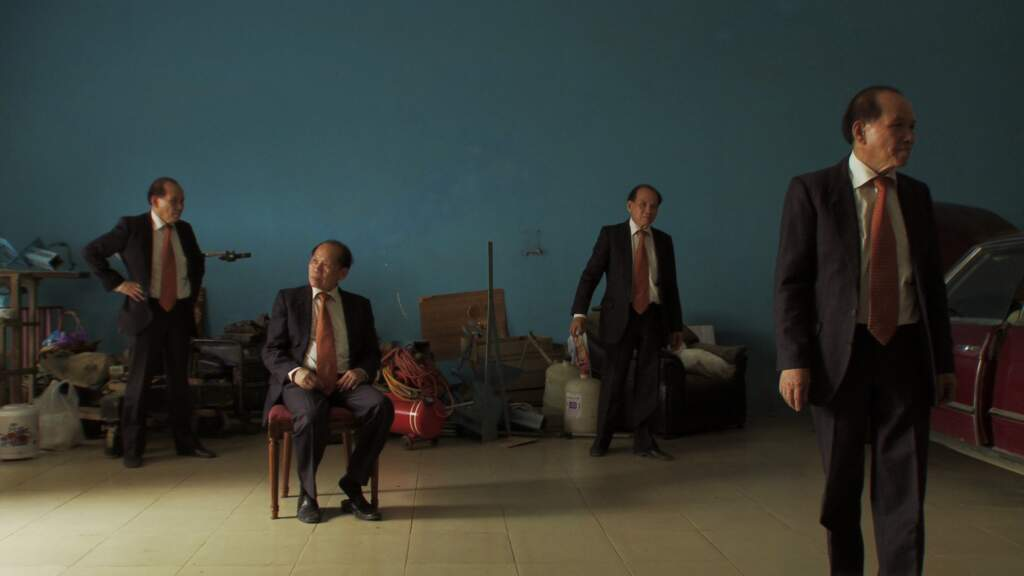 Wideshot still from Golden Slumbers. A dark, dusk background with outlines of buildings. A group of four white men in suits and red ties standing, spread out and looking in different directions. One is sat on a chair, three are standing,