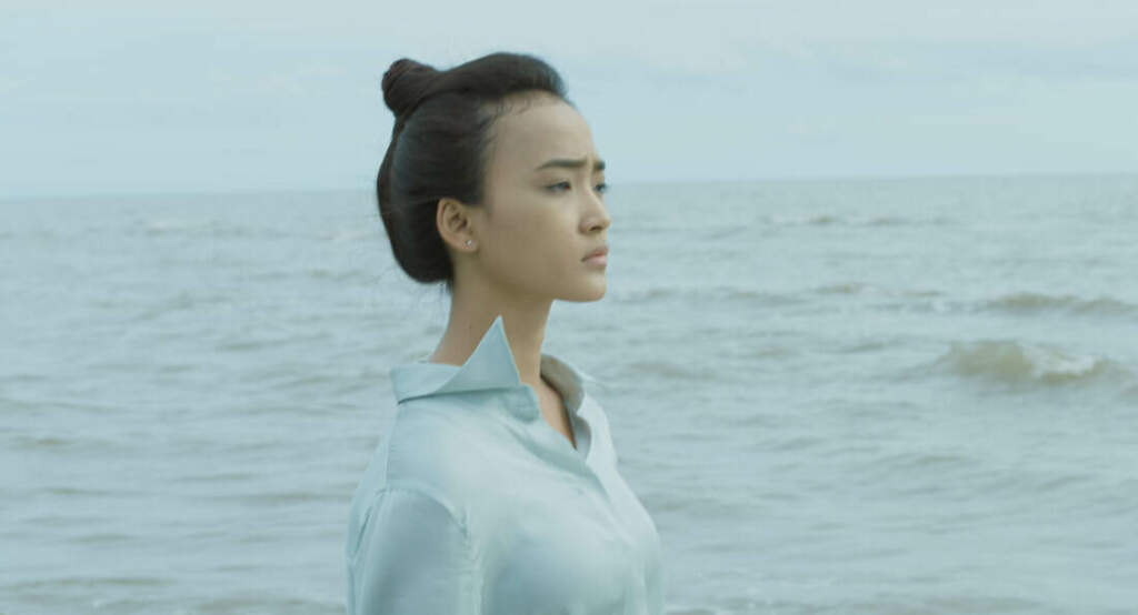 Film still from California Dreaming. A wideshot of Sarita, a young woman of colour with black hair up in a bun. She's wearing a white shirt and is standing up and looking out into the distance. Behind her is the ocean horizon. The skies are grey, and the water a grey blue.
