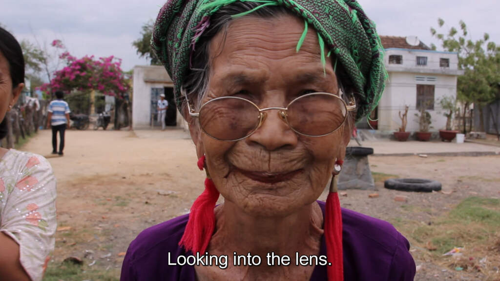 Wideshot still from Letters from Panduranga. Close up shot of the shoulders and face of an elderly Vietnamese person. They're wearing glasses, a scarf-like headpiece, and long red, threaded earrings. The background is a small village.