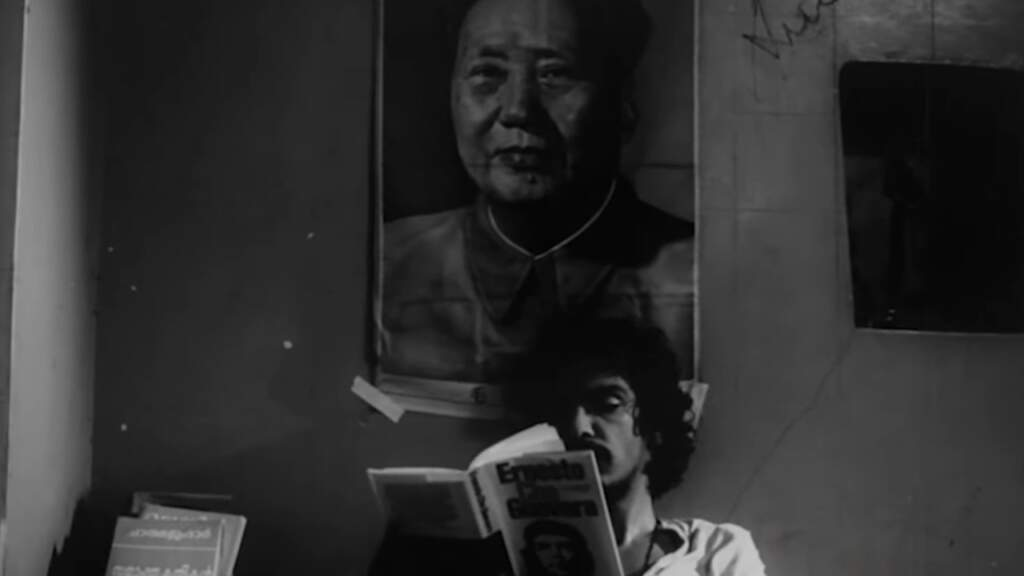 Film still from Amma Ariyan (Report to Mother). A dark, black and white wideshot. The top half of a man with a scruffy beard and shaggy, long hair reading a book on Che Guevara. Behind him on the wall. a large portrait poster of Mao Zedong