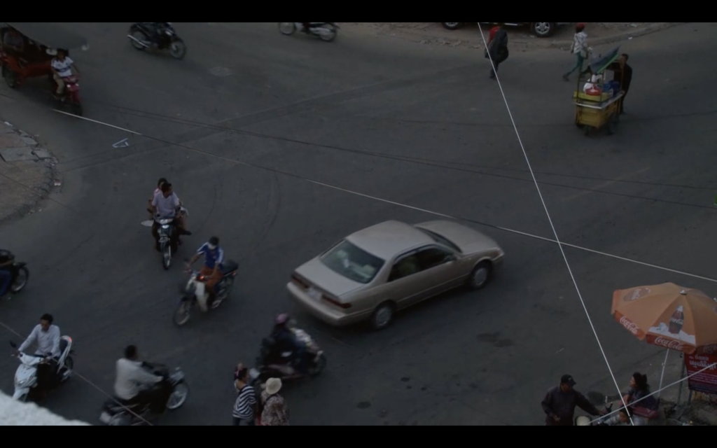 Film still from Boding. A bird eye's view shot of a white car in a car park, with several people on motorbikes spread around the car.