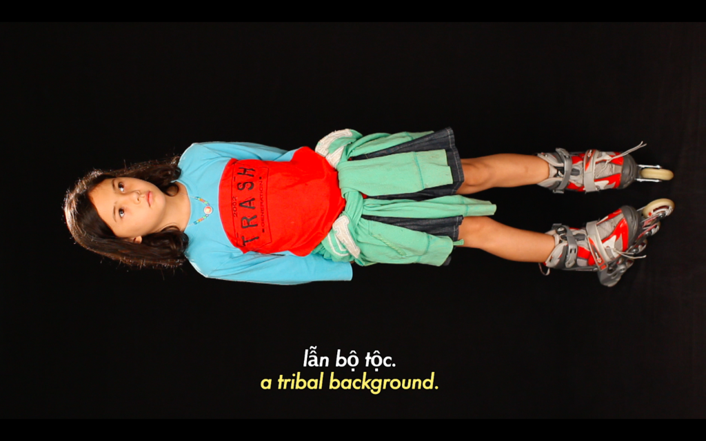 """Still from Fifth Cinema. The background is black, and in the centre near the bottom, there's small white letters with accents, words that aren't English. They read """"'lẵn bộ tộc"""". Below this is the English translation """"a tribal background"""" in small yellow writing. Above this writing, a young Vietnamese woman at 90 degrees counter clockwise. They're wearing roller skates, a blue and red sweater, and a green jumper tied around their waist."""