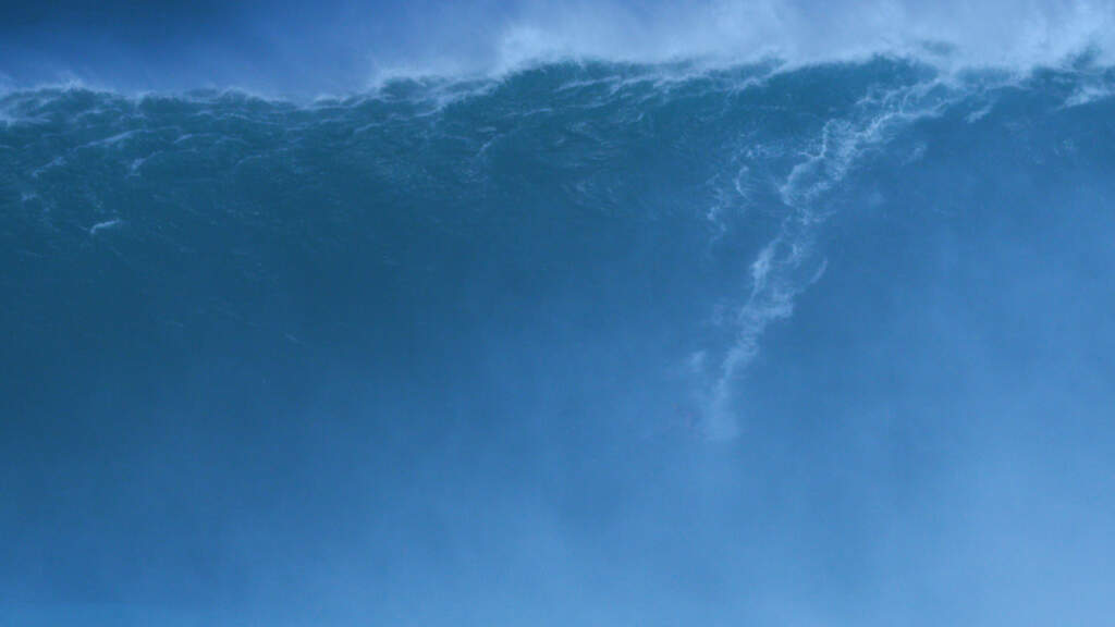Still from Rock Bottom Riser. A wideshot of a huge deep blue wave. It looks like its merging into the blue sky above it.