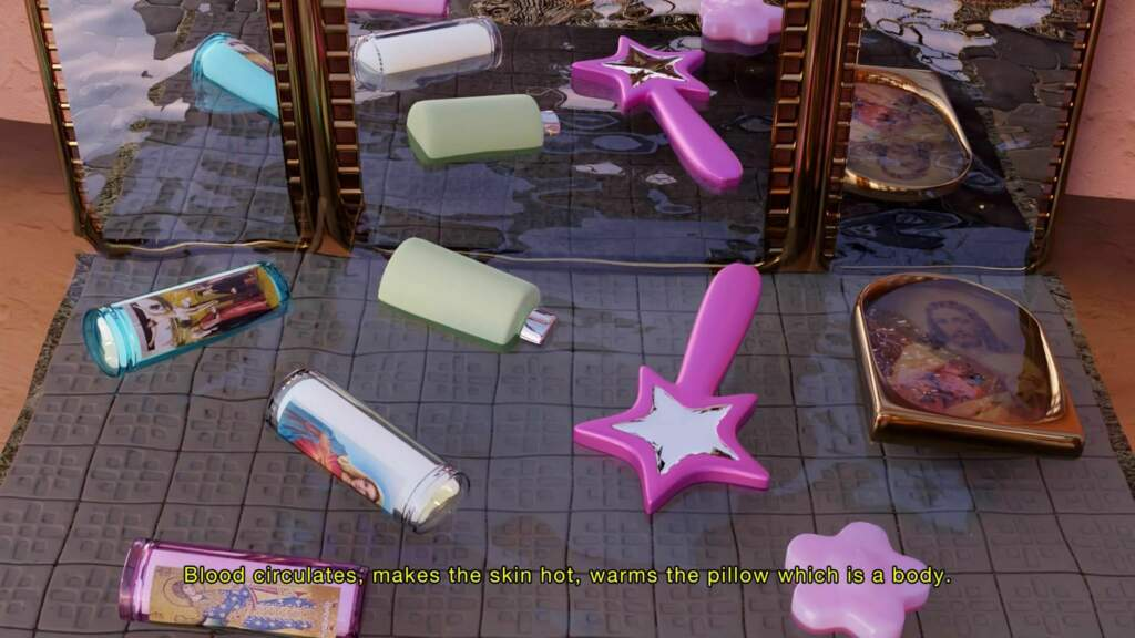 Wideshot from A Body Is A Body Is A Body. A downwards shot of the floor, with scattered items such as a purple, star shaped wand, a white bottle, a lilac object in the shape of flower petals, and a framed painted portrait. Behind the items, a wide mirror placed on the ground, and the reflection of the items can be seen in the mirror. The items are laid out on a grey rug, on wooden floorboards.