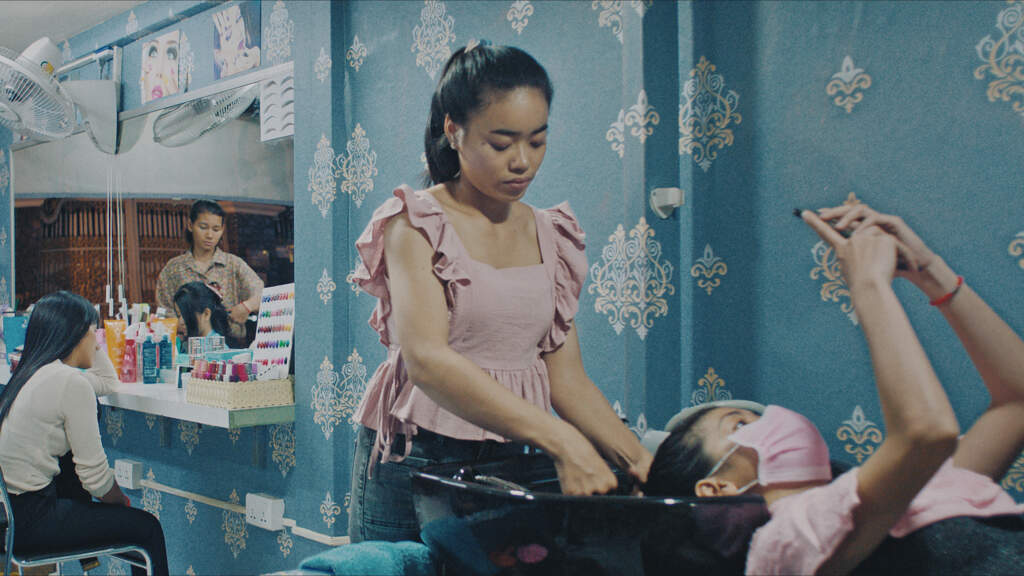 Still from Sunrise in My Mind. Wideshot of a beauty salon in Cambodia. On the right, a Cambodian women wearing a mask is getting her hair washed in a basin by another Cambodian woman who is standing up. The customer is lying back with her hair in the basin and she's on her phone.