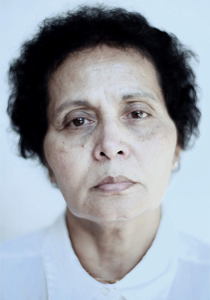 Portrait still from Foreign Quarters. A close up portrait shot of an older woman, with short black hair, wearing a white shirt. The portrait is cut off at the shoulders. She has a tired, somewhat sullen expression on her face. She's looking directly into the camera.