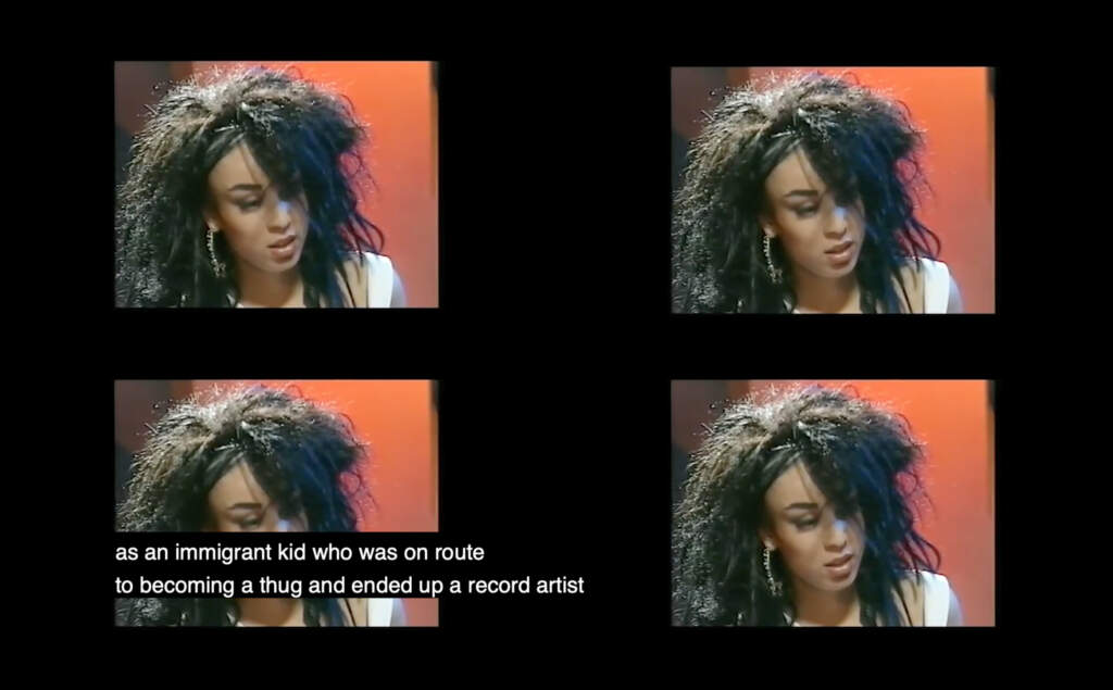 Film still from Passion of Remembrance. A four way split television set, with four images of a Black woman with afro hair in a square frame. Her background is orange.