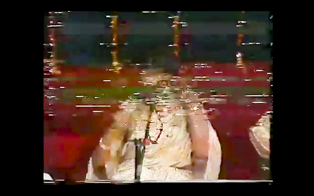 Film still from If From Every Tongue It Drips. Abstract illustration portraying the lower half of a person's white dress and arms. The still has a black square outline, the subject appears to be behind a square window. The subject's background is dark red. Where their head should be, there's multi-coloured lines and blurriness.