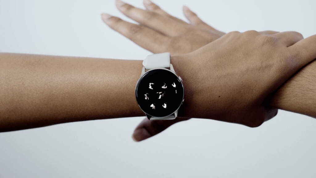 Still from Show Me Other Places. Shot of a forearm and hand reaching and grabbing someone else's wrist. The person grabbing the other person's wrist is wearing a watch. The background is a beige white.