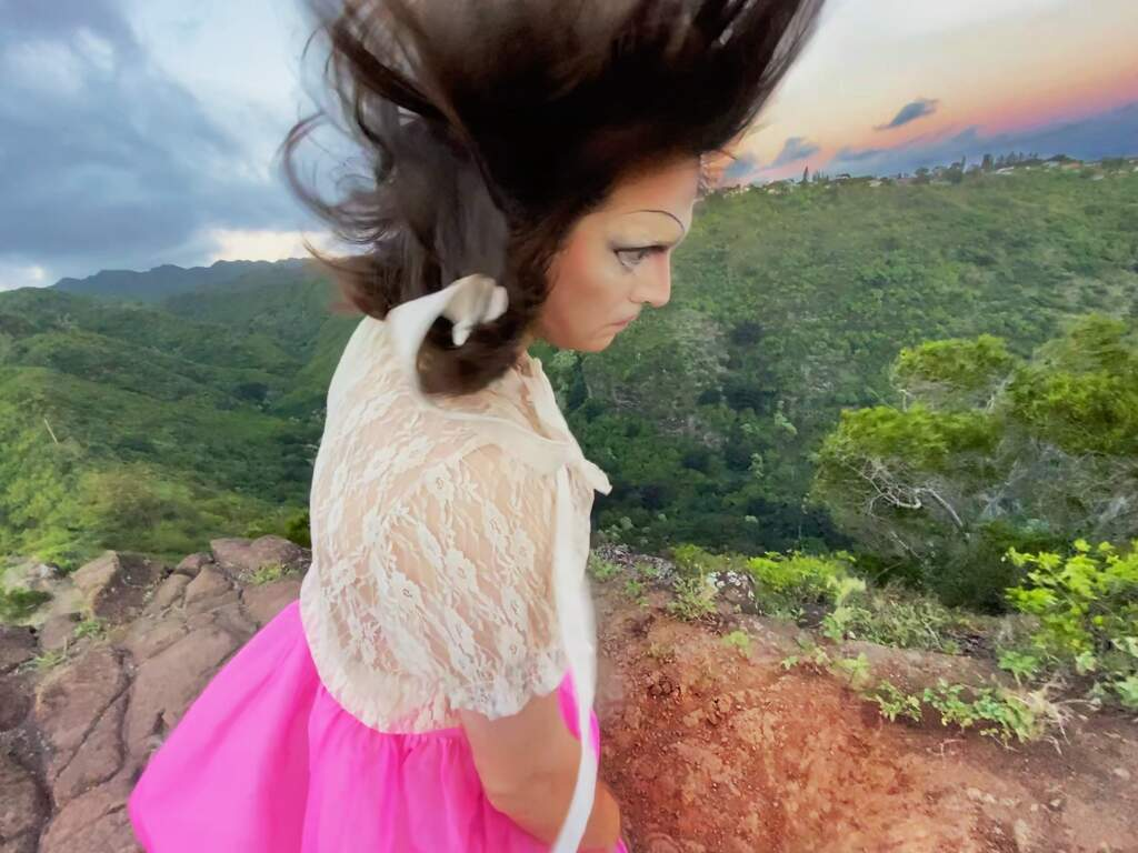 Still from Hair Is A Piece of Body. The background is made up of forestry and outlines of hills. The subject is a white person wearing a white cardigan and pink skirt, although the rest of their outfit and body is cut off at the hip. Their side profile is facing the camera, and their dark hair is being swept by wind, blowing upwards. It appears they are standing on a hill or the edge of one.