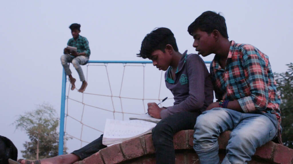Wideshot film still from Entrance Exam. On the right hand side, two young boys sitting side by side, one of them writing something on a notepad, and the other peering over the boy's shoulder to read what he's writing. On the left, in the distance. a young boy sitting on a high metal fence with a book in his hands..