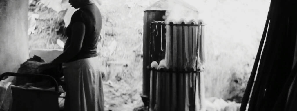 Film still from If I Were Any Further Away I'd Be Closer To Home. Black and white wideshot. On the left, a woman wearing a dark top and a white skirt is touching the wall.