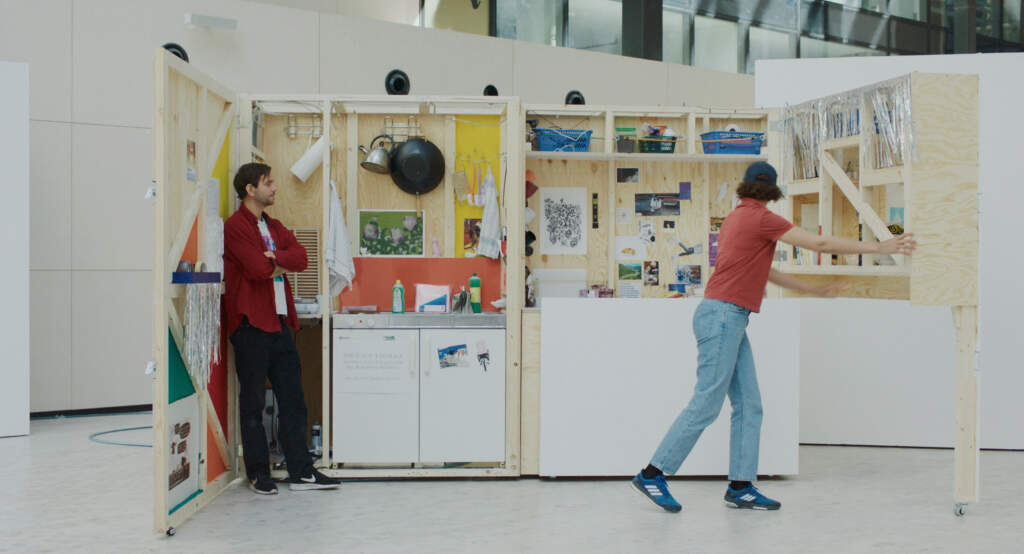 Film still from Manifesto. Wideshot of a white classroom with colourful artwork on the wall. On the left, a man in a red open shirt is leaning against the wall with his arms crossed. On the right, a person in blue jeans and an orange top is walking in motion and looking at the art.